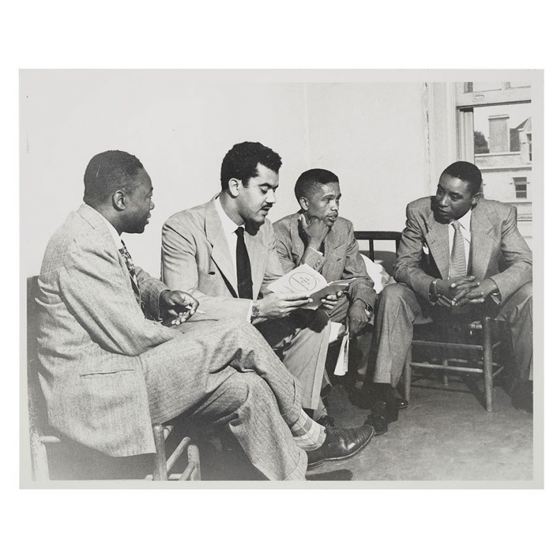 Four men sit in a dorm room.