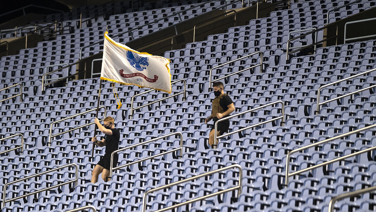 A student holding an Army flag runs stairs in Kenan Stadium.